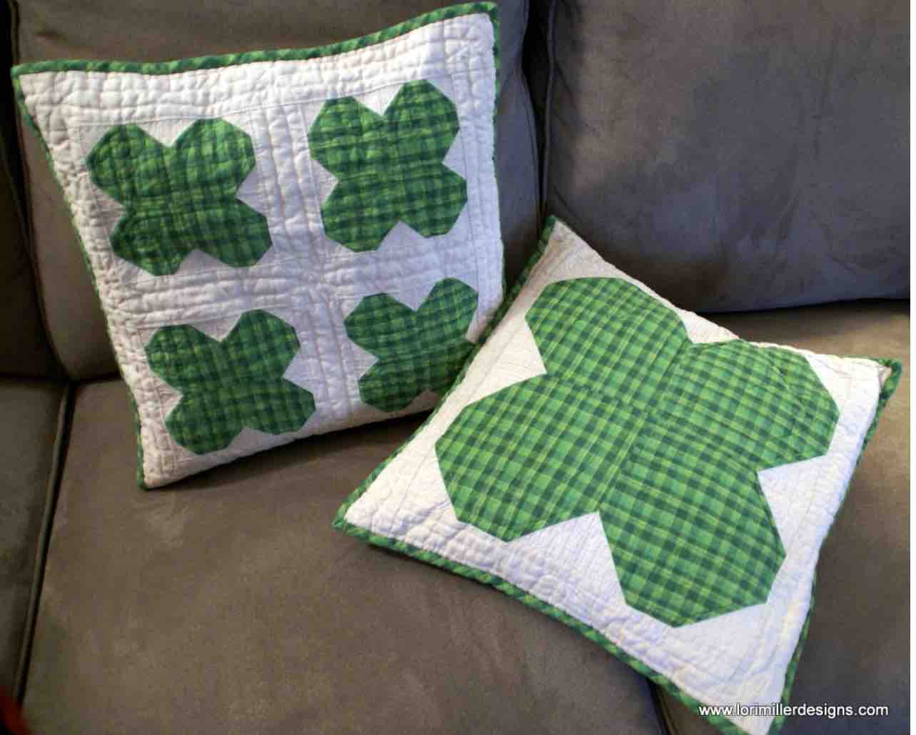 Two square pillows on a couch. One pillow has four quilted shamrocks and the other has one large quilted shamrock.